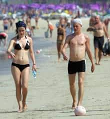 Tourists soak up the sun while walking along Patong Beach in Phuket, Thailand, in December 2005. Recent studies indicate that vitamin D, which is produced naturally in the body through exposure to the sun's ultraviolet rays, can extend and improve people's lives.