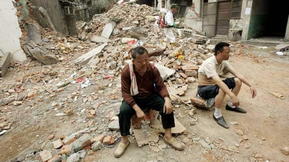 Earthquake survivors rest on Tuesday after hunting for their belongings in the rubble in the town of Hanwang, in China's Sichuan province.