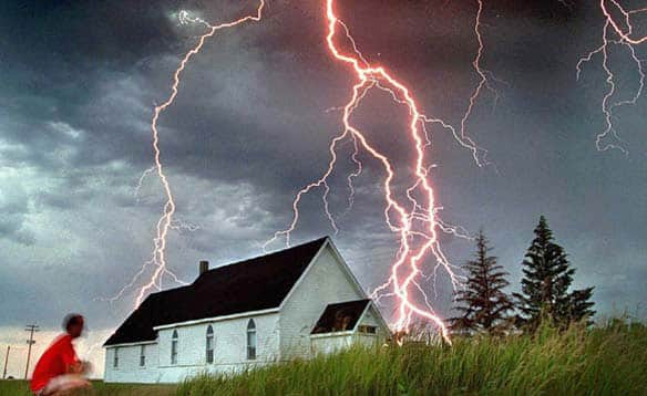 Neil Fraser watches as lightning hits beyond a church in Rosser, Man., as a severe electrical storm made its way across southern Manitoba in July 1995.