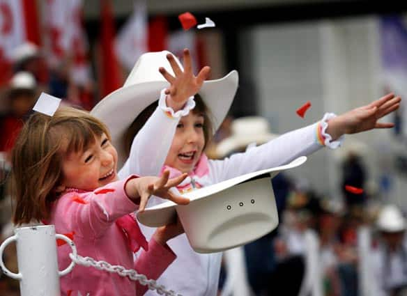 Thousands came out to enjoy the annual Calgary Stampede parade, including Vanessa Jenkins, 6, left, and Sophie Hunchak, who threw confetti on the route.