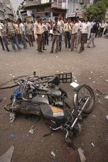 People stand around the site of an explosion in Ahmadabad.