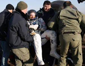 The ground crew assists U.S. space tourist Richard Garriott after the Russian Soyuz space capsule landed near the town of Arkalyk in northern Kazakhstan on Friday, Oct. 24, 2008.