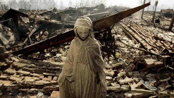 A statue stands in front of a home destroyed at the Oakridge Mobile Home Park in the northern San Fernando Valley area of Los Angeles.