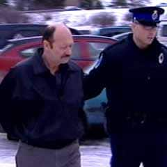 Bruce Leyte, seen being escorted to court in Corner Brook last November, has pleaded guilty to mischief and fraud.