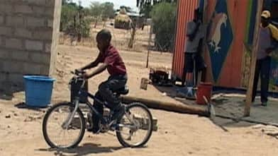 A young African boy tests his 'new' bike from Canada in Namibia.