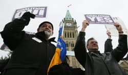 Two postal workers hold pro-coalition signs as they rally on Parliament Hill in Ottawa on Thursday.