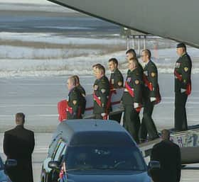 The casket of one of the fallen soldiers is unloaded off a military airplane during a ramp ceremony at CFB Trenton on Monday.