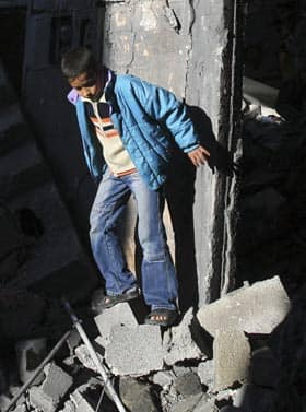 A Palestinian boy inspects the rubble at a building in Rafah refugee camp, southern Gaza Strip, following Israeli attacks Tuesday.