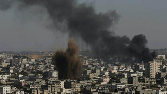 Smoke caused by explosions from Israeli attacks rises from buildings on the outskirts of Gaza City on Tuesday.