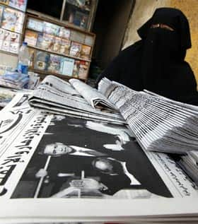 An Egyptian newspaper vender sits in front of newspapers fronted by pictures of the inauguration of Barack Obama, in Cairo.