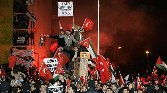 Supporters wave Turkish and Palestinian flags outside the Ataturk International Airport in Istanbul early Friday.