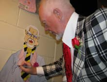 Don Cherry autographs one of hundreds of ties and images of the Coach's Corner star at Campbellton Middle School.