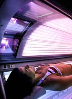 Glenda Fuster lies in a tanning booth at the Run to the Sun tanning salon in Anchorage, Alaska.