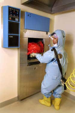 This 2006 photo released by the Public Health Agency of Canada shows a scientist, Dr. Adrienne Meyers, putting waste into a double-door autoclave to sterilize it with heat and pressure before the material leaves the Containment Level 4 laboratory of the National Microbiology Laboratory in Winnipeg.