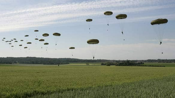 British paratroopers from the 3rd Parachute Battalion land in a wheat field outside the village of Ranville, western France, Friday, as troops re-enact part of the bloody Allied landings of D-Day.