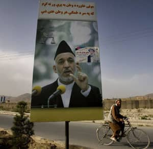 An Afghan cycles past an election poster for Afghanistan President Hamid Karzai in Kabul on Tuesday.