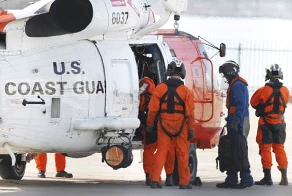 U.S. Coast Guard divers board a MH-60 Jayhawk helicopter early Friday. They were searching for as many as nine people off the San Diego coast following a mid-air collision.