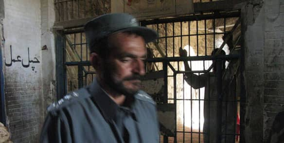 A prisoner leans against an entrance to the wing where political prisoners are kept at Sarposa prison in Kandahar, Afghanistan.
