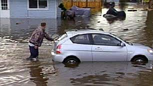 Residents rescue a car from the flooded streets.