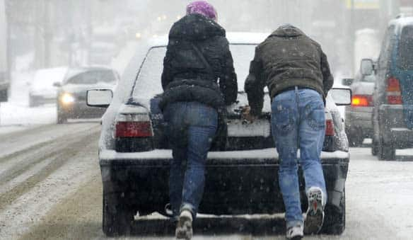 Two people push a car as snow falls on a street a in Gelsenkirchen, Germany on Saturday.