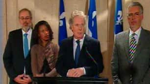 Premier Jean Charest, at microphone, accompanied by, from left, International Relations Minister Pierre Arcand, Immigration Minister Yolande James and Public Security Minister Jacques Dupuis, promises Quebec will help Haiti.