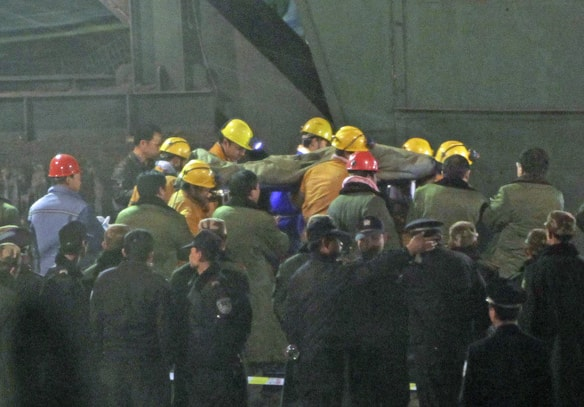 A survivor is rescued from the flooded Wangjialing coal mine early Monday.