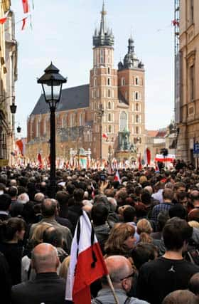 Tens of thousands of people listen to the church service for the late Polish president and his wife.