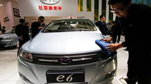 A worker cleans an all-electric BYD e6 at a Beijing auto show this year. About 100 test vehicles will be put on the road as taxis in the southern Chinese city of Shenzhen by June, with a launch on the west coast of the U.S. by the end of the year.