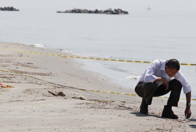 Lonely warrior. Barack Obama counting tar balls on a Louisiana beach in May 2010. (Larry Downing/Reuters)
