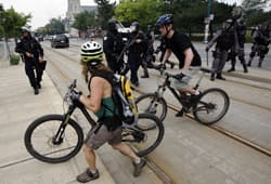 Riders are turned off a street by police in riot gear as they take part...