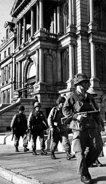 A patrol of soldiers with semi-automatic rifles and one with a machine gun marches past Montreal City Hall on Friday, Oct. 16, 1970, as the War Measures Act was implemented. (LaPresse/Canadian Press)