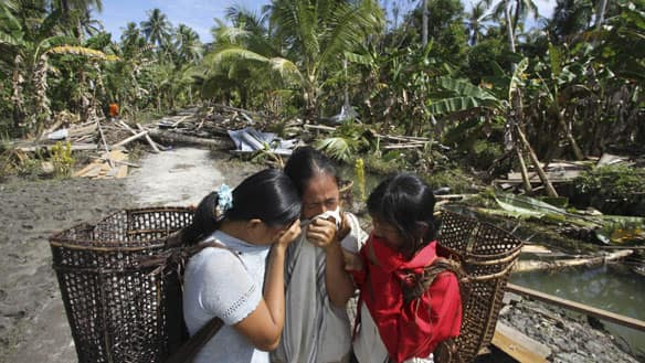 A woman who lost her house and husband in the earthquake-triggered tsunami weeps with her daughters on Pagai Island, in the Mentawai Islands, Indonesia, on Thursday.