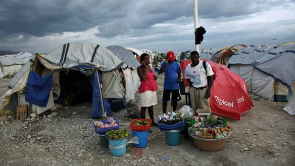 Earthquake victims buy groceries at an improvised store in Camp Corail, north of Port-au-Prince, on Monday.