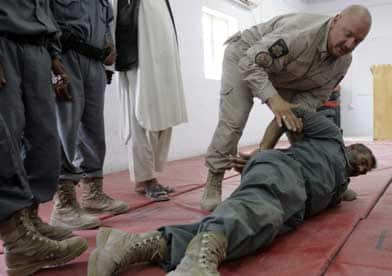 Not just Canada's military who are training. An instructor with Correctional Services Canada demonstrates how to apprehend a prisoner to Afghan prison security officers in August 2009. (Allauddin Khan/Associated Press)