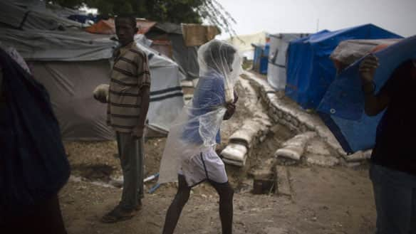 A woman covers herself with a plastic sheet Friday as she walks in the rain brought by Hurricane Tomas at a camp set up for people displaced by the January earthquake in Port-au-Prince, Haiti.