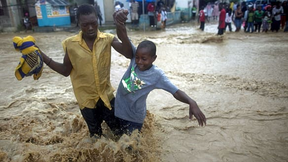 People wade through a flooded street during the passing of Hurricane Tomas in Leogane, Haiti, on Friday.