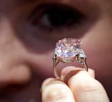 An employee of Sotheby's auction house holds a 24.78 carat pink diamond mounted as a ring, last seen on the market some 60 years ago.