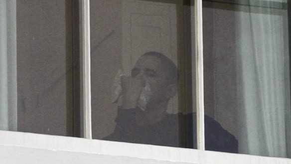 U.S. President Barack Obama, with an ice pack over his mouth, looks out a second floor window of the White House during the arrival of the official White House Christmas tree on Friday.