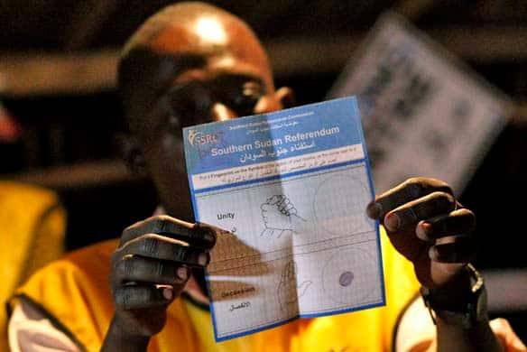 An election official shows an independence ballot as votes are tallied at a polling station in Juba, in Southern Sudan, on Saturday.