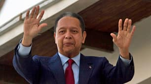Former dictator Jean-Claude Duvalier waves from the balcony of the guest house where he is staying in Port-au-Prince.