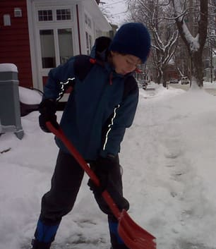 Niall Moan, 10, shovels the sidewalk outside his home in Halifax on Wednesday. Most public schools on the mainland are closed because of the weather.