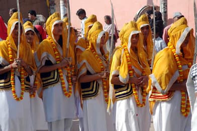 Sikh women hold ceremonial kirpans during a religious procession in the northern Indian city of Allahbad, Nov. 13, 2005. Both female and male Sikhs may be initiated, and then required by their faith to wear a kirpan.