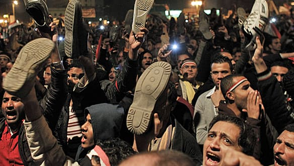 Anti-government protesters hold their shoes as they react in Cairo's Tahrir Square to Egyptian President Hosni Mubarak's televised statement on Thursday that he won't step down.
