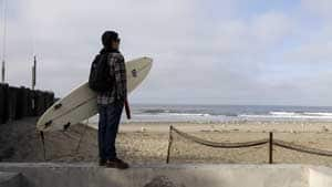 Mark Fontes, of Costa Mesa, Calif., holds his board while watching waves on the Balboa Peninsula in Newport Beach, Calif., Friday.