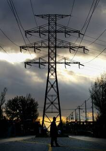 A pedestrian stands under a hydro tower in downtown Toronto in November 2002. Electricity costs rose dramatically that year after the Harris government tried to create a freer electricity market.