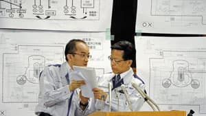 Japan's nuclear safety agency official Hidehiko Nishiyama, right, consults a staff member during a news conference on Tokyo Electric Power Co.'s Fukushima Daiichi nuclear power plant, in Tokyo on  Friday.