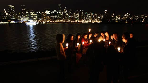 A group of friends in Vancouver's Stanley Park hold candles as they gather for last year's Earth Hour.