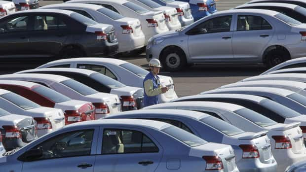 In this file photo, a worker checks Yaris compact sedans, set for export to North America, at a Toyota plant in Miyagi prefecture in northern Japan.