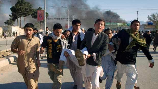 Afghans carry a man who was wounded in an attack on the UN's office in Mazar-i-Sharif, north of Kabul.