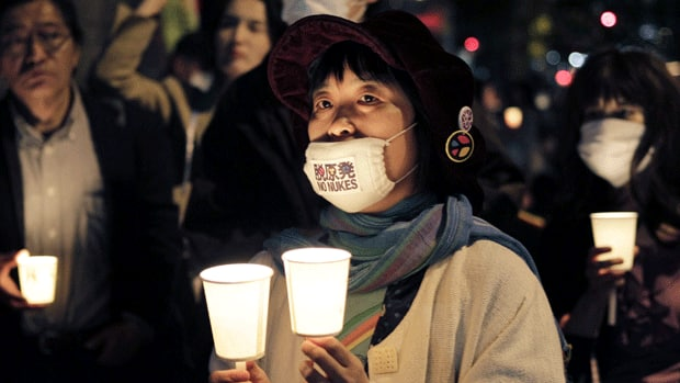 A woman wearing a No Nukes mask attends a candlelight vigil marking the 25th anniversary of the Chornobyl nuclear disaster in Ukraine. She was among protesters in Tokyo on Tuesday gathered in front of the headquarters of Tokyo Electric Power Co., which operates the stricken Fukushima Daiichi nuclear power plant.